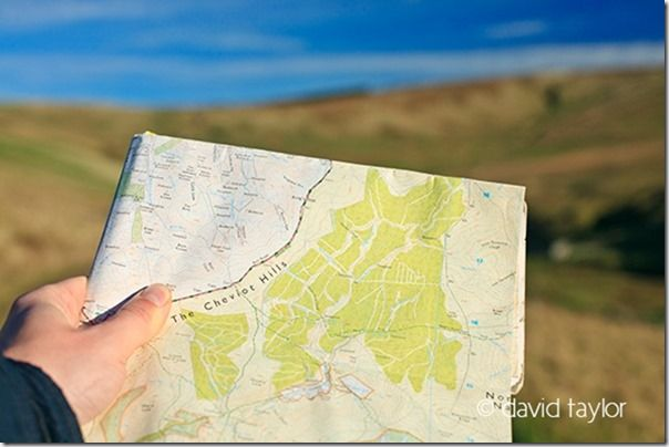 Walker holding an Ordnance Survey map of the Cheviots hills, Northumberland National Park, England. OS REF: NT 883143, hiking safety, hiking essentials, hiking safety tips, what to wear hiking, navigational aids, landmarks, Warm, cold, weather, climate, snow, heat, exhastion