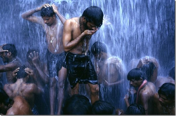 Followers of the Shiva sect of Hinduism (known as Shaivites or Shaivas) ritually bathe at a Hindu Bathing festival at Courtalam waterfall, Tamil Nadu, India. The town is dedicated to Lord Thirukutralanathar (Lord Siva). The Chittar River flows through the town into the main falls called the Peraruvi.