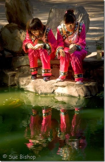 girls feeding fish at prince gongs palace