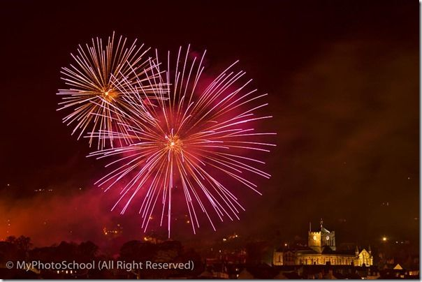 Firework display held in the Sele, a park in Hexham, with the floodlit Abbey in the foreground, Northumberland, England