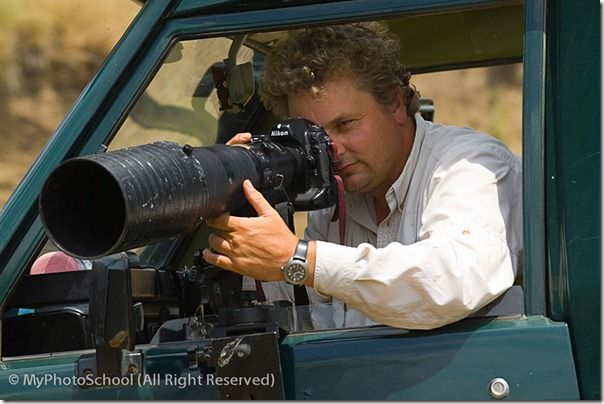 Wildlife photographer David Tipling photographing with a telephoto lens from safari vehicle in Masai Mara Kenya July 2005