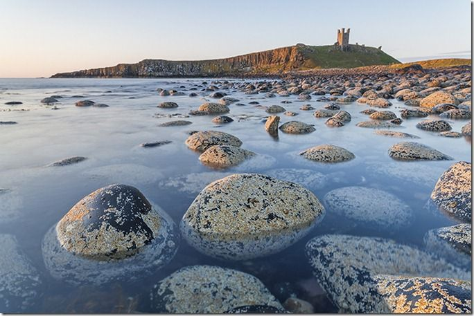 The view of Dunstanburgh Castle from the north bay showing the Lilburn Tower and Greymare rocks, Northumberland, England