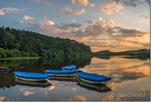 Boats on Crag Lough in Hadrian's Wall Country on a summer's evening, Northumberland, England