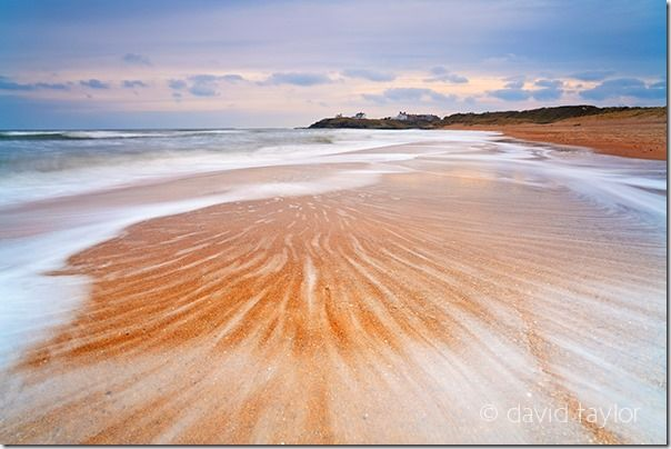Waves washing over the sandy beach near Seaton Sluice on the south Northumberland coast, England